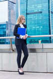 Business woman holding folder with documents in hand against the background of skyscrapers Royalty Free Stock Images
