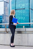 Business woman holding folder with documents in hand against the background of skyscrapers Stock Image