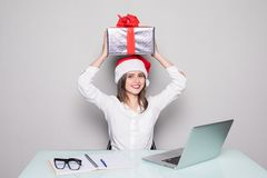 Young business woman holding gift box over head while working on desk office concept office christmas and happy new year. Business woman holding gift box Royalty Free Stock Photos