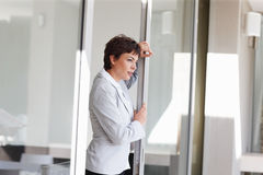 Business woman holding a glass door and standing Royalty Free Stock Image