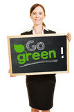 Business woman holding go green concept. On a blackboard in her hands Royalty Free Stock Photos