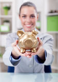 Business woman holding gold piggy bank,focus on piggy bank. Smiling business woman, holding gold piggy bank Stock Photo