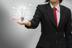 Business woman holding idea lamp. With gray background Royalty Free Stock Photo