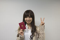 Business woman holding Japanese passport with Victory sign Royalty Free Stock Photography