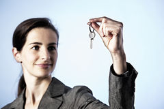 Business woman holding key between fingers Stock Image