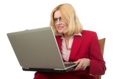 Business Woman Holding Laptop. Beautiful business woman in a red suit sitting in a chair holding and looking very closely to a laptop computer Royalty Free Stock Photos