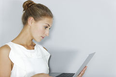 Business woman holding laptop. Attractive young business woman holding a laptop royalty free stock photography