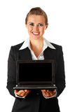 Business woman holding laptop with blank screen. Smiling modern business woman holding laptop in hand with blank screen isolated on white stock photos