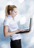 Business woman holding laptop computer. Young adult attractive business woman holding laptop computer on blue blur background Stock Photos