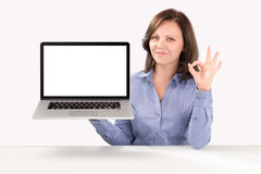 Business woman is holding a laptop. In one hand and by other hand showing ok gesture, business concept royalty free stock images