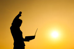 Business woman holding laptop at sunset silhouette. Stock Photography