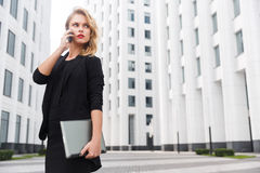 Business woman holding laptop and talking on phone. Business woman holding laptop and serious talks on phone outdoors stock photos