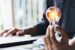 Business woman holding light bulb on the desk in office and using  computer in  financial,accounting,energy,idea concept