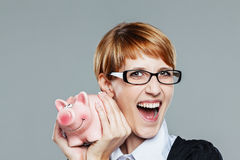 Business woman holding a little piggy bank and smiling. On grey Royalty Free Stock Photos