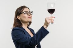 Business woman is holding and looking at a glass of red wine. White studio background Stock Image