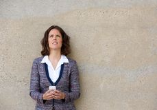 Business woman holding mobile phone and looking up Stock Photography