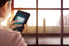 Business woman holding modern tablet with Tax word on the scree Stock Photography