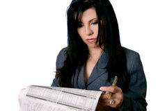 Business woman holding a newspaper and pen. A business woman reading a newspaper with a serious or cocentrated expression Royalty Free Stock Photography