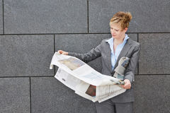 Business woman holding newspaper in windy weather Royalty Free Stock Photo