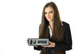 Business Woman Holding Office Sign. Business woman holding a gray office sign Royalty Free Stock Photo