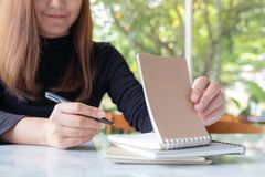 A business woman holding and opening a blank notebook to write on table with green nature background. Closeup image of a business woman holding and opening a stock photo