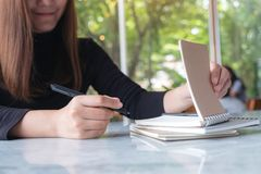 A business woman holding and opening a blank notebook to write on table with green nature background. Closeup image of a business woman holding and opening a stock photos