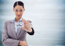 Business woman holding out card showing idea doodles against blurry blue wood panel Royalty Free Stock Image