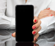 Business woman holding phone in hands, howing to you a blank pho Stock Images