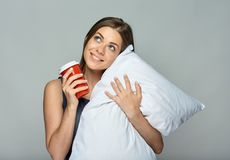 Business woman holding pillow with coffee cup looking up. Royalty Free Stock Photo