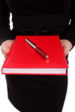 Business woman holding a red agenda and a red pen Royalty Free Stock Photo