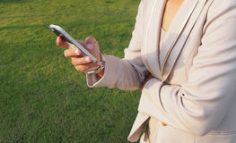 Business woman holding smart phone. With green grass background Stock Images