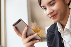 Business woman holding smartphone in her hand and checking email royalty free stock image