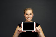 Business woman holding a tablet computer - isolated over a dark Royalty Free Stock Images
