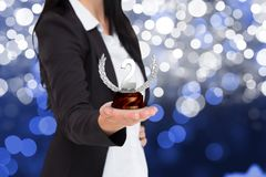 Business woman holding trophy against fireworks background Stock Images