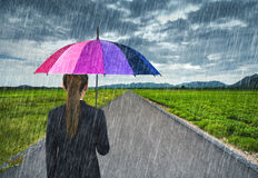 Business woman holding umbrella with falling rain at country roa Stock Photo