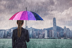 Business woman holding umbrella with falling rain at victoria ha Stock Photo
