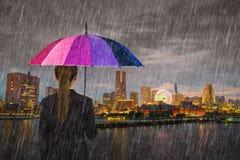 Business woman holding umbrella with falling rain at Yokohama ci Stock Image