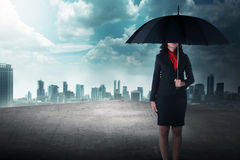 Business woman holding umbrella standing on the rooftop Royalty Free Stock Images