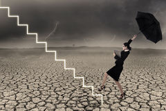 Business woman holding umbrella in stormy weather. Businesswoman is walking up line of stairs while holding umbrella in stormy weather stock images