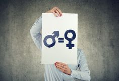 Business woman holding a white paper with male and female symbol on gray wall background stock photos