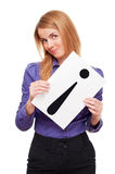 Business woman holding white sheet of paper. Young business woman holding white sheet of paper with big black exclamation point up side down in studio Royalty Free Stock Photography