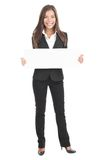 Business woman holding white sign / poster. Businesswoman holding a white empty banner or poster in full length. Beautiful mixed race chinese / caucasian woman Stock Image