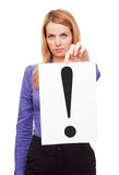 Business woman holding whiye sheet of paper. Young business woman holding white sheet of paper with big black exclamation point in studio Stock Photography