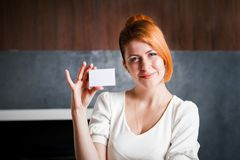 Business woman holds a business card. Inside the office Stock Photos
