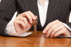 Business woman holds house key for handing over Stock Photos