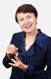 The business woman holds a key. With a charm in the form of a small house on white background Royalty Free Stock Image