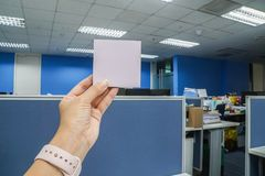 Business woman holds mock up postit sticky note in office with left hand. Close up business woman holds mock up postit sticky note in office with left hand Royalty Free Stock Images