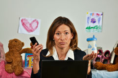 Business woman holds phone and baby bottle Royalty Free Stock Photos