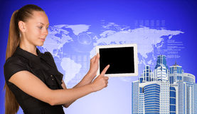 Business woman holds tablet PC, pointing at blank. Screen. High-rise buildings beside.On blue background with hi-tech graphs and world map. Business concept Stock Images