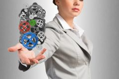 Business woman holds up a mechanism of gears Stock Image